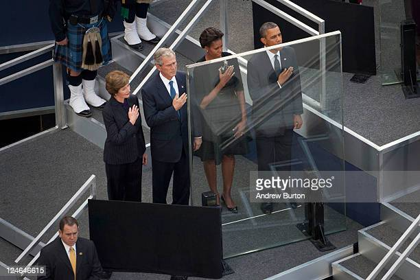 Former first lady Laura Bush former President George W Bush first lady Michelle Obama and US President Barack Obama stand for the national anthem...