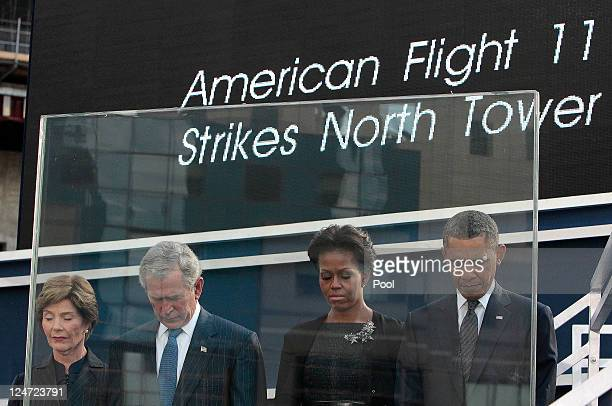Former first lady Laura Bush former President George W Bush first lady Michelle Obama and President Barack Obama bow their heads during a moment of...