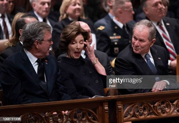 Former First Lady Laura Bush wipes her eye during a moment of levity as former President George W. Bush and his brother Jeb Bush look on during the...