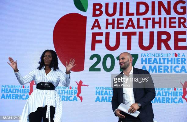 Former First Lady Michelle Obama waves as former White House chef and Senior Policy Advisor for Nutrition Policy Sam Kass looks on during the...