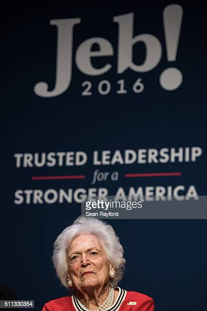 Former first lady Mrs Barbara Bush listens to her son Republican presidential candidate Jeb Bush at a campaign event February 19 2016 in Greenville...