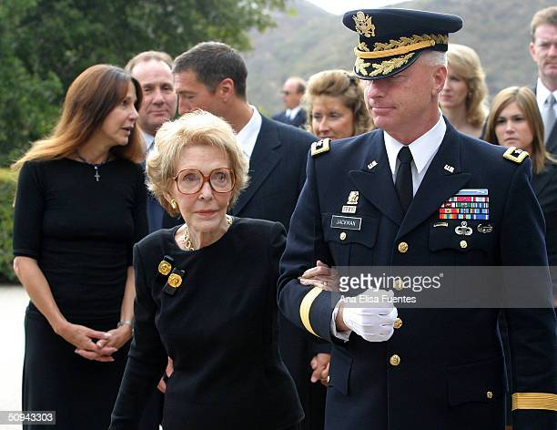 Former first lady Nancy Reagan is escorted by Maj Gen Galen B Jackman with Patti Davis and Ron Reagan following while the casket of former President...