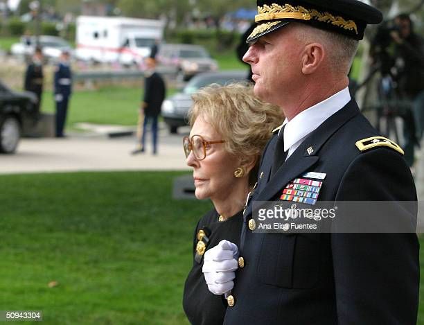 Former first lady Nancy Reagan is escorted by Maj Gen Galen B Jackman while the casket of former President Ronald Reagan is placed into the hearse...