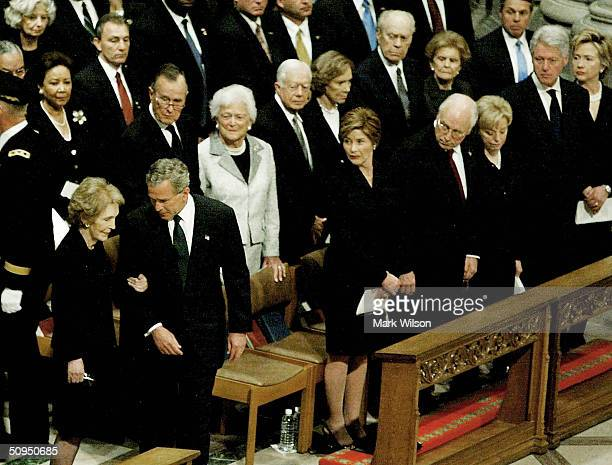 Former first lady Nancy Reagan is escorted by US President George W Bush to her seat during former President Ronald Reagan's State Funeral at the...