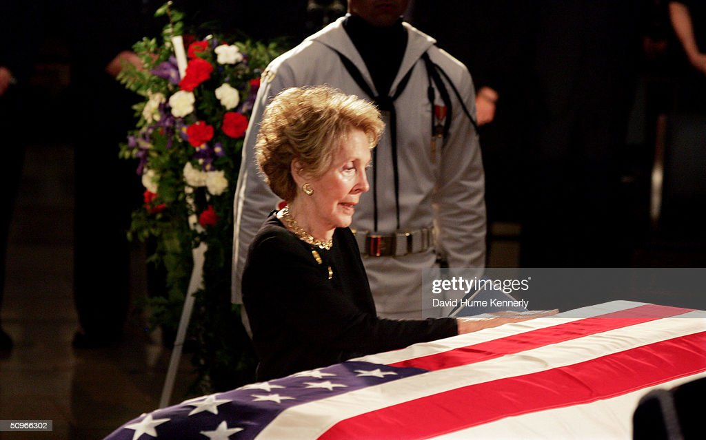 Former first lady Nancy Reagan touches the casket of her husband, the 40th President of the United States, Ronald Reagan as he lies in state inside the Rotunda of the U.S. Capitol June 9, 2004 in Washington, DC.
