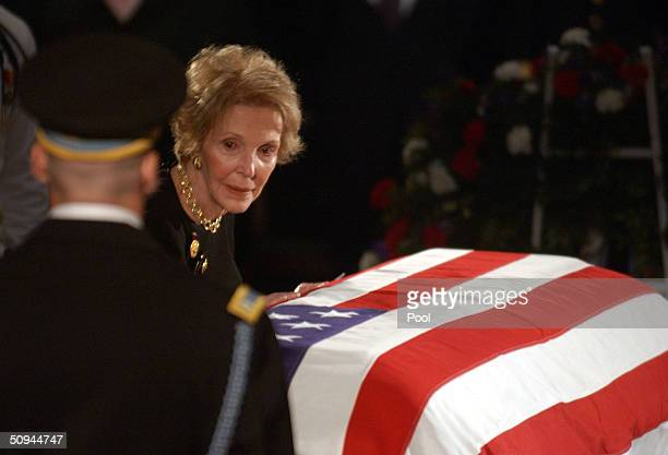 Former first lady Nancy Reagan touches the casket of her husband, former U.S. President Ronald Reagan, during his state funeral on Capitol Hill June...