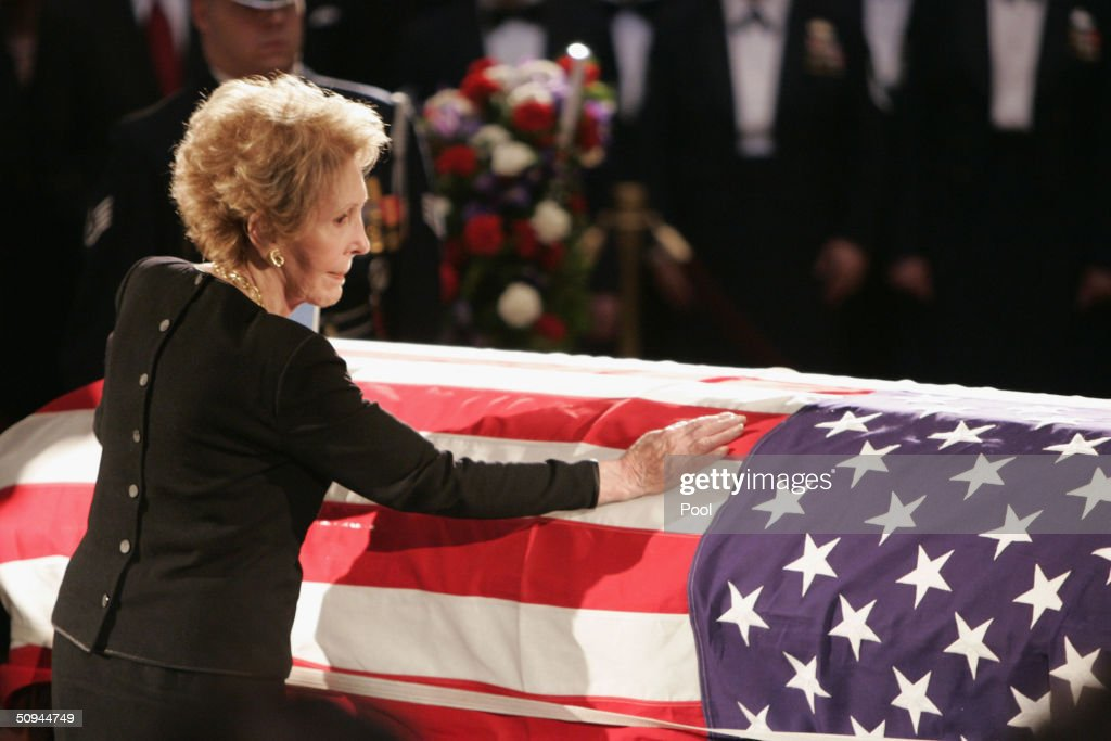 Former first lady Nancy Reagan touches the casket of her husband, former U.S. President Ronald Reagan, during his state funeral on Capitol Hill June 9, 2004 in Washington, DC. Reagan's body will lie in state throughout the night until June 10.