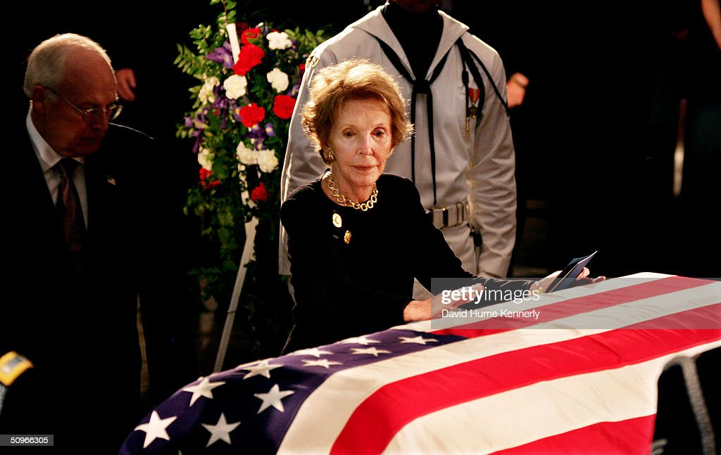 Former first lady Nancy Reagan, with Vice President Dick Cheney behind her, touches the casket of her husband, the 40th President of the United States, Ronald Reagan as he lies in state inside the Rotunda of the U.S. Capitol June 9, 2004 in Washington, DC.