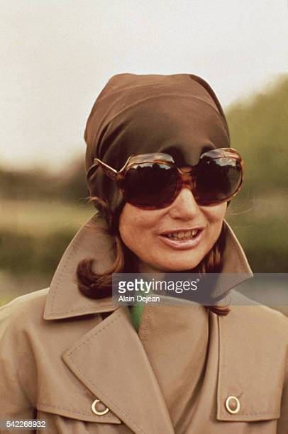 Former First Lady of the United States Jacqueline Kennedy Onassis wears dark sunglasses and a kerchief to protect her privacy