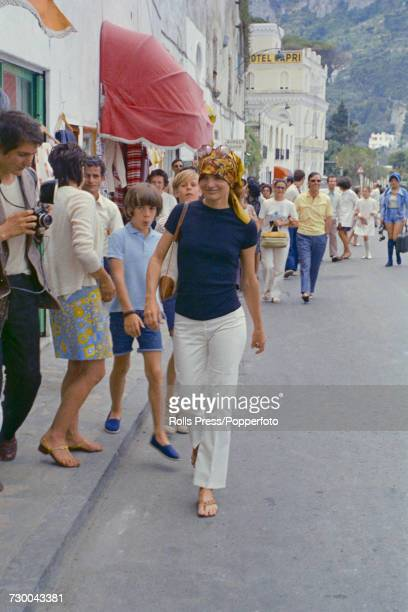 Former First Lady of the United States Jacqueline Kennedy Onassis pictured wearing white slacks a blue tshirt and a headscarf as she walks down a...