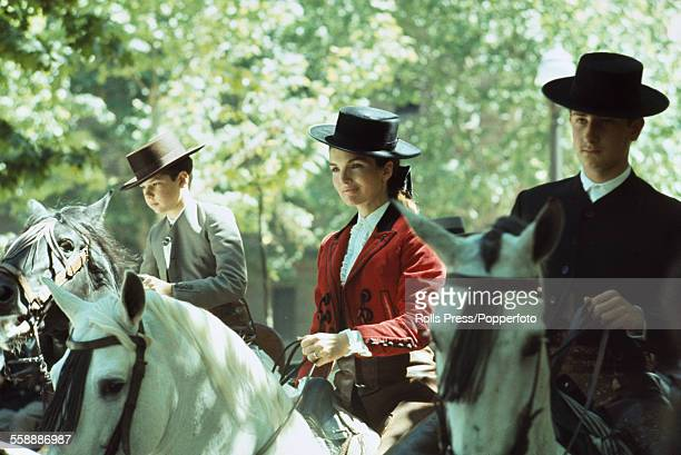 Former First Lady of the United States Jacqueline Kennedy pictured wearing a picador style jacket and brimmed hat whilst riding a white horse at the...