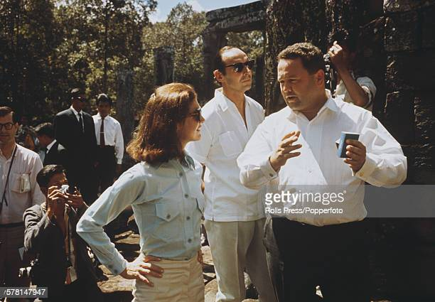 Former First Lady of the United States Jacqueline Kennedy pictured wearing a man's button down shirt and hip hugging slacks as she visits the ruins...