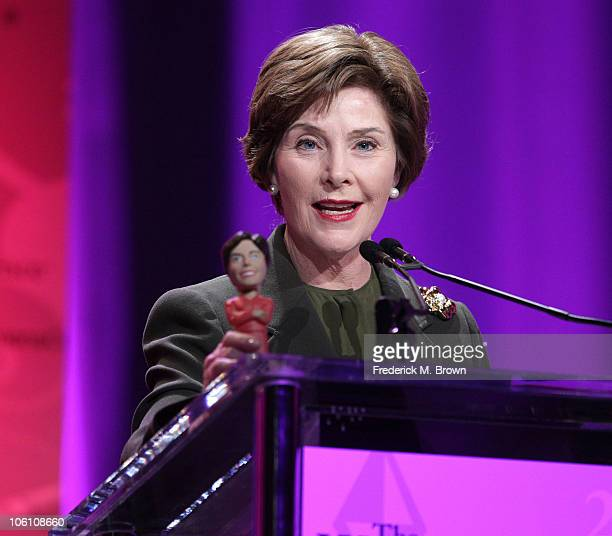 Former First Lady of the United States Laura Bush with her bobblehead doll speaks during the Maria Shriver Women's Conference at the Long Beach...