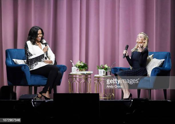 Former First Lady of the United States Michelle Obama left and actress Reece Witherspoon have a laugh together on stage during Becoming An Intimate...
