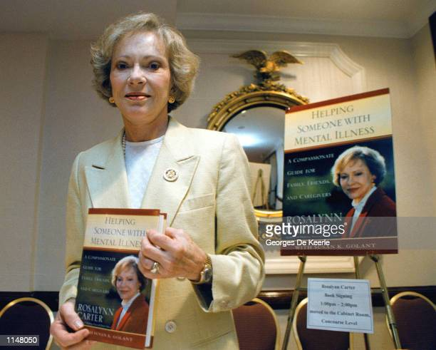 Former first lady Rosalynn Carter holds a copy of her latest book dealing with mental illness Helping Someone with Mental Illness July 17 1998 in...