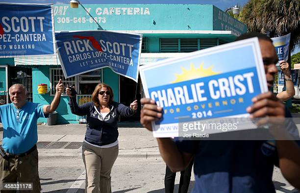 Former Florida Governor and now Democratic gubernatorial candidate Charlie Crist supporters and Republican Governor Rick Scott supporters stand near...