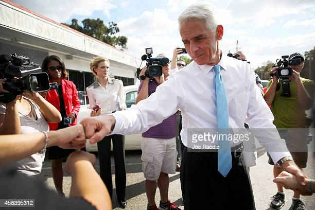Former Florida Governor and now Democratic gubernatorial candidate Charlie Crist fist bumps with a supporter as he makes an election day phone bank...