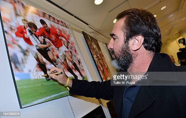Former football player Eric Cantona signs exhibition's pictures during a visit to the Golden Foot 2012 photo exhibition at Grimaldi Forum on October...