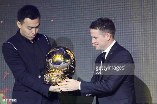 Former football player Michael Owen presents the player of the year award to Feng Xiaoting during Chinese Footballer of The Year Awards on December...