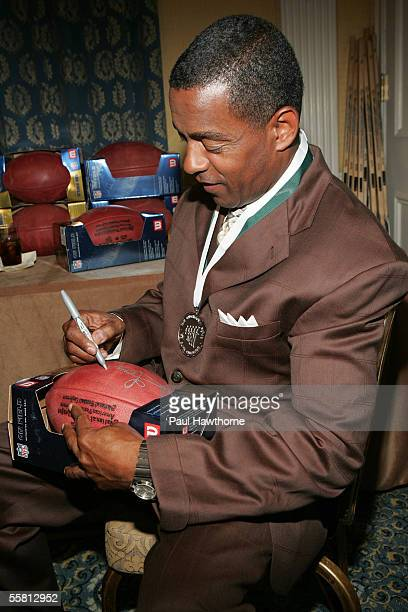 Former Football Player Tony Dorsett autographs a football at the Great Sports Legends Dinner at the Waldorf Astoria September 27 2005 in New York...
