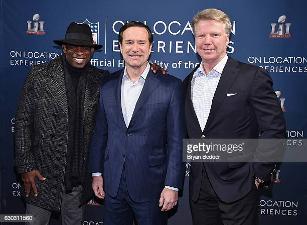 Former football players Deion Sanders and Phil Simms pose for a photo with CEO of On Location Experiences John Collins during On Location...