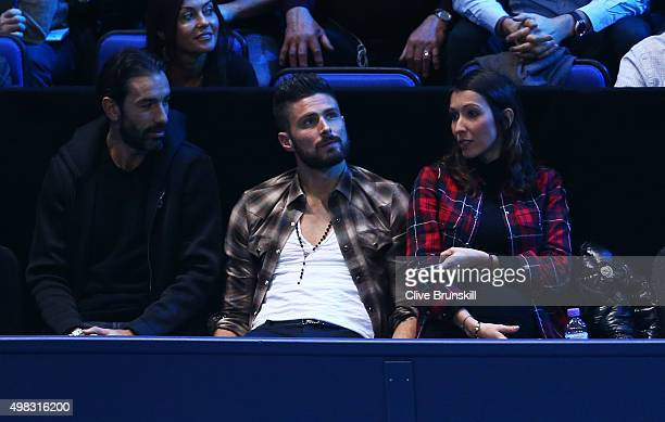Former footballer Robert Pires footballer Olivier Giroud of Arsenal and France and his wife Jennifer attend the men's singles final between Roger...