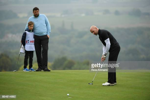 Former footballer Steve Stone putts as former cricketer Steve Harmison watches during the pro am ahead of the British Masters at Close House Golf...