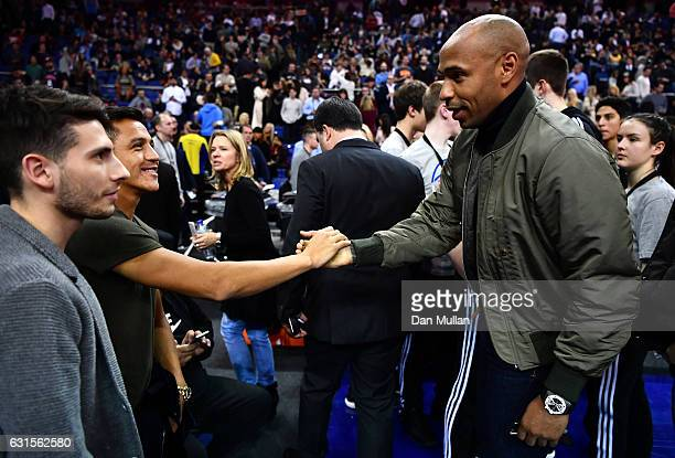 Former footballer Thierry Henry speaks to Arsenal player Alexis Sanchez looks on during the NBA match between Indiana Pacers and Denver Nuggets at...