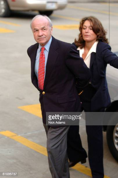 Former Former Enron CEO Kenneth Lay is escorted from a car and to a federal court by a law enforcement official after being indicted for wire fraud...