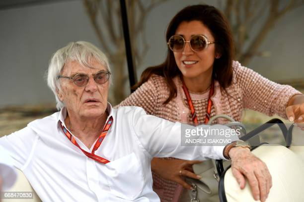 Former Formula 1 boss Bernie Ecclestone and his wife Fabiana Flosi ride a golf cart ahead of the Formula One Bahrain Grand Prix at the Sakhir circuit...