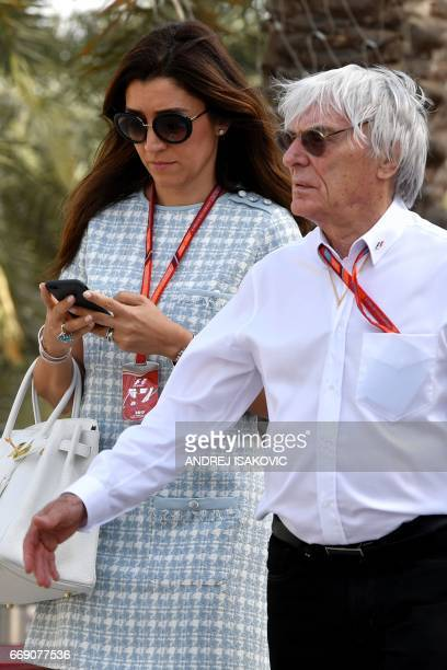 Former Formula 1 boss Bernie Ecclestone and his wife Fabiana Flosi walk in the paddock ahead of the Bahrain Formula One Grand Prix at the Sakhir...