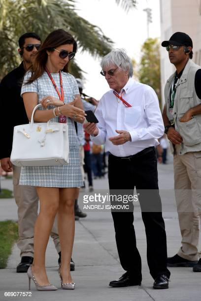 Former Formula 1 boss Bernie Ecclestone and his wife Fabiana Flosi stand in the paddock ahead of the Bahrain Formula One Grand Prix at the Sakhir...