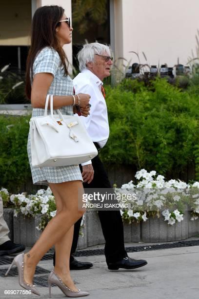 Former Formula 1 boss Bernie Ecclestone and his wife Fabiana Flosi walk in the paddock ahead of the Bahrain Formula One Grand Prix at the Sakhir...