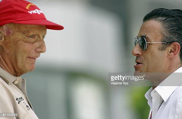 Former Formula One Champion Niki Lauda chats with former Formula One driver Jean Alesi in the paddock during qualifying for the Malaysian Formula One...