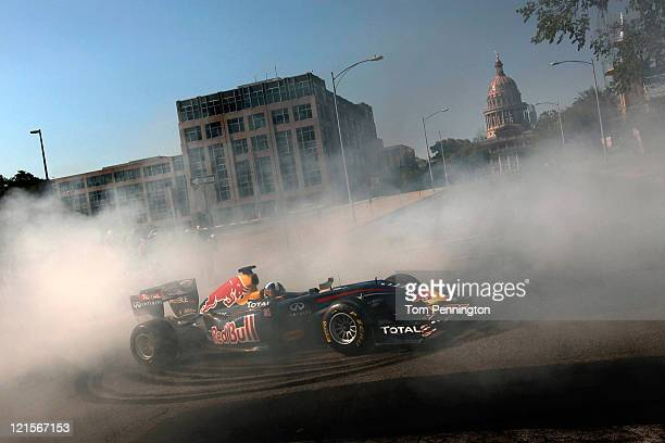 Former Formula One driver David Coulthard of Great Britain completes a burnout while driving the Red Bull Show Car in fornt of the Texas Capitol...