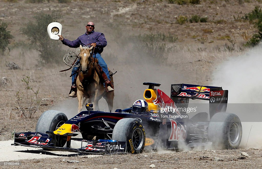 Former Formula One driver David Coulthard of Great Britain drives the Red Bull Show Car while being chased by a cowboy at a ranch on August 19, 2011 in Johnson City, Texas.