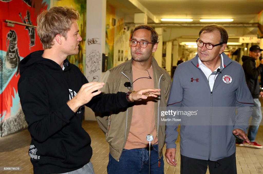 Former Formula One Worldchampion Nico Rosberg (L) talks to german singer and songwriter Bosse (C) and Ewald Lienen, technical director of St. Pauli before the viva con aqua social e-cart race at Millerntor Stadium on August 22, 2017 in Hamburg, Germany.