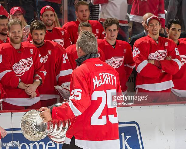Former forward Darren McCarty of the Detroit Red Wings 1997 Stanley Cup Team walks with the Stanley Cup in front of the current team during the...