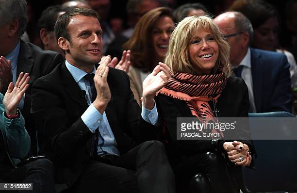 Former French Economy Minister Emmanuel Macron and his wife Brigitte applaud during a meeting of his political movement 'En Marche' on October 18...