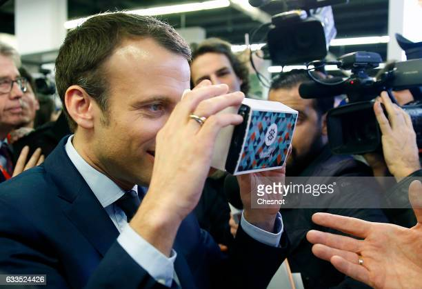 """Former French Economy Minister, founder and President of the political movement """"En Marche !"""" Emmanuel Macron tries a device for cell phone during..."""