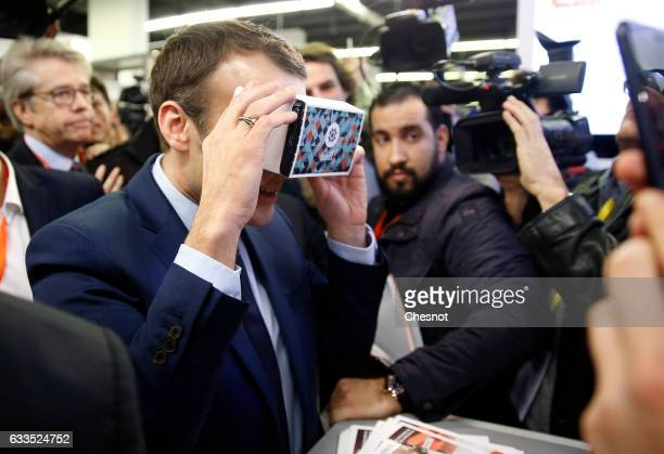 Former French Economy Minister founder and President of the political movement 'En Marche ' Emmanuel Macron tries a device for cell phone during his...