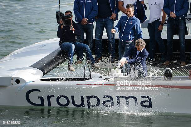 Former French F1 pilot Alain Prost breaks a bottle of champagne on the new multihull 'Groupama Team France' during its inauguration on July 11 2016...