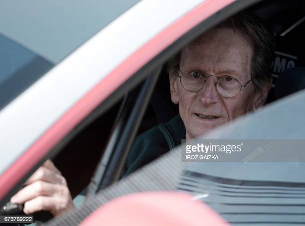 Former French F1 pilot JeanPierre Jabouille sits inside the Tesla Electric GT car during a demonstration on the PauArnos circuit in Pau southwestern...