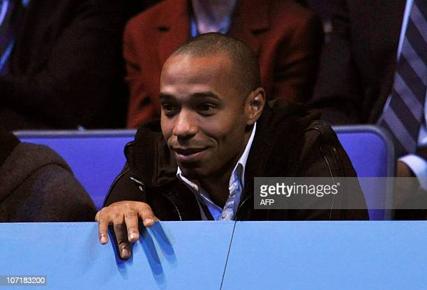 Former French football paly thiery Henry watches as Switzerland's Roger Federer plays against Spain's Rafael Nadal , during their singles final...