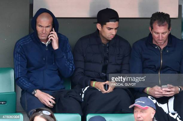 Former French football player Zinedine Zidane and his son Enzo sit in the stands during Croatia's Mirjana LucicBaroni and France's Alize Cornet's...