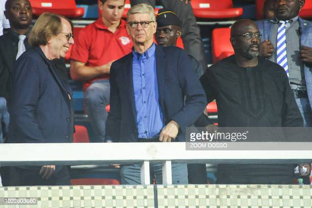 Former French football players and coaches Claude LeRoy and Arsene Wenger arrive with Liberian President George Weah at the stadium to attend a...