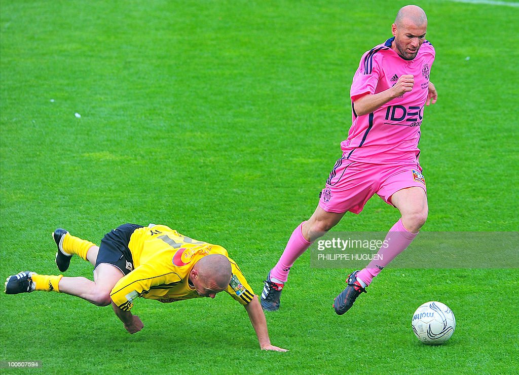 Former French football star Zinedine Zidane (R) vies with Calais' defender Donat Darcy during the football exhibition match Calais vs. Varietes Club de France, on May 25, 2010 at the Epopee stadium in Calais, northern France. This exhibition match between Calais and a team made up of French 1998 World Cup champions stands to commemorate amateur team of Calais epic run to the final of the 2000 Coupe de France.