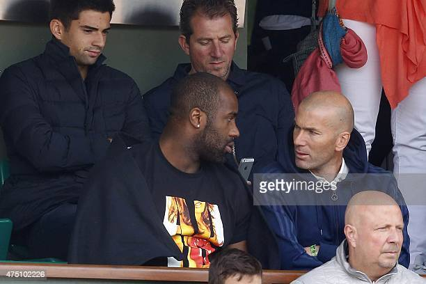 Former French football Zinedine Zidane his son Enzo and French judo champion Teddy Riner sit in the stands at the Roland Garros 2015 French Tennis...