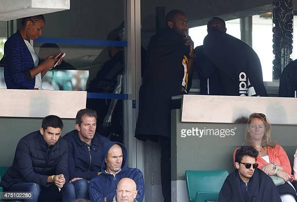 Former French football Zinedine Zidane his son Enzo sit in the stands as French judo champion Teddy Riner leave at the Roland Garros 2015 French...