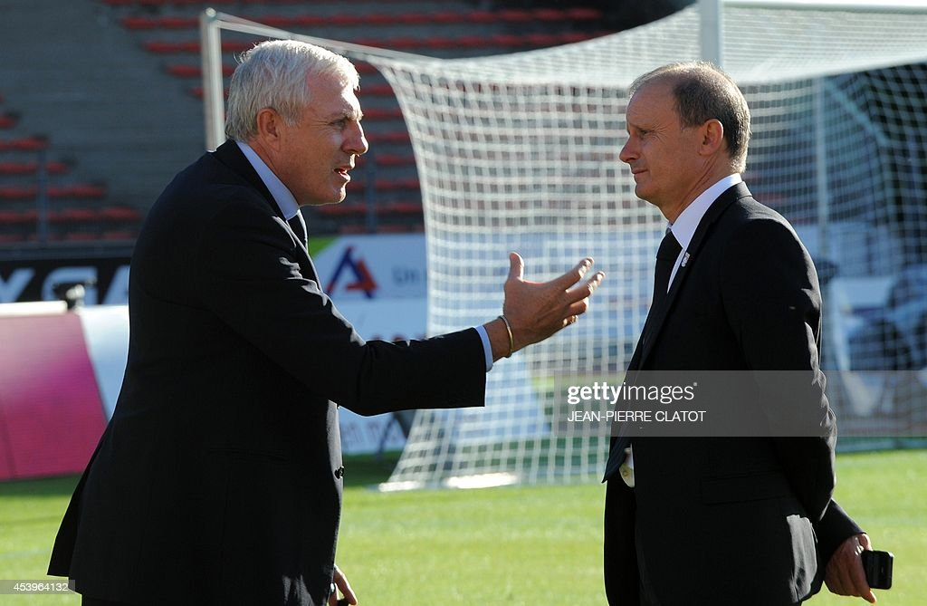 Former French footballer Luis Fernadez (L) speaks with Evian TG's French president Joel Lopez before the French L1 football match between Evian Thonon Gaillard and Paris Saint-Germain (PSG) at the Parc des Sports stadium in Annecy, southern France, on August 22, 2014.